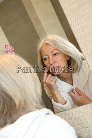 mulher senior de aplicar o hidratante